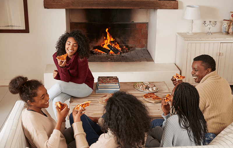 Gathered around fireplace eating pizza iStock 846735214 800px